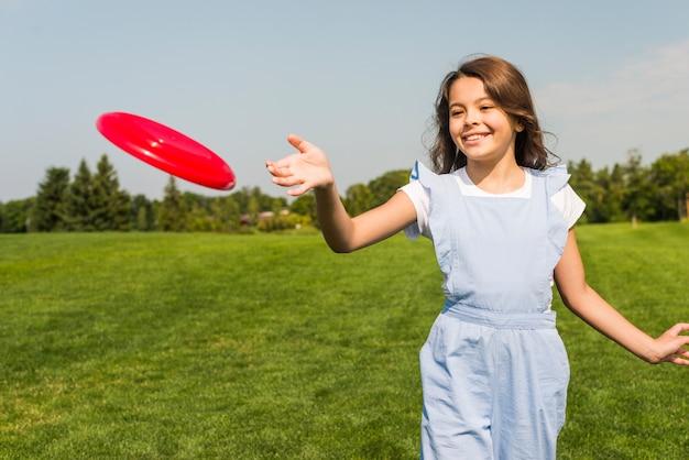 Nettes kleines mädchen, das mit rotem frisbee spielt