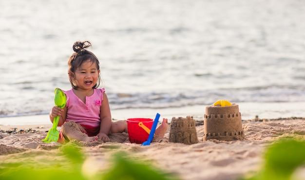 Nettes kleines mädchen, das sand mit spielzeugsandwerkzeugen spielt