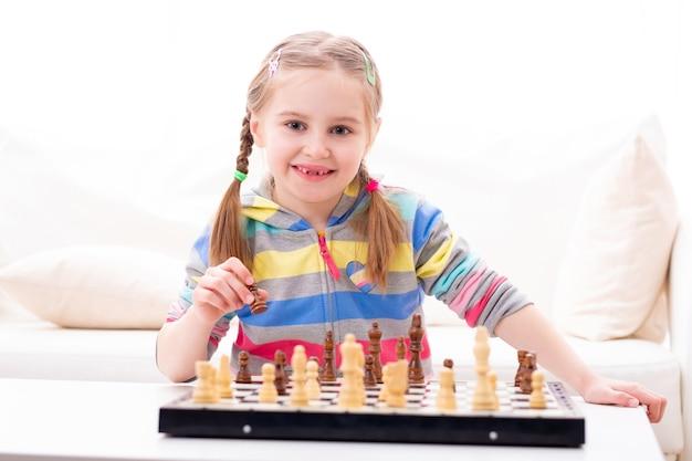 Nettes kleines mädchen, das schach spielt