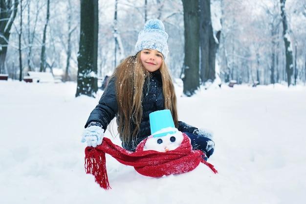 Nettes kleines mädchen, das schneemann im winterpark macht