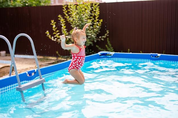Nettes kleines mädchen, das sich darauf vorbereitet, ins blaue wasser zu springen und spaß im pool zu haben