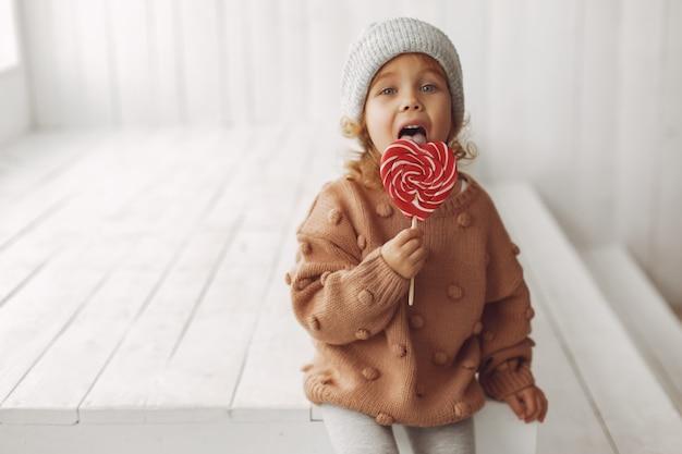 Nettes kleines mädchen, das sitzt und süßigkeiten isst