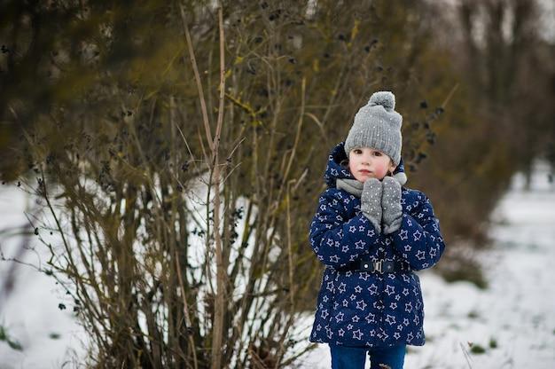 Nettes kleines mädchen, das spaß draußen am wintertag hat.