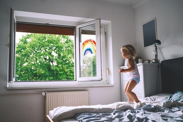 Nettes kleines mädchen, das spaß hat, auf dem bett auf dem hintergrund des fensters mit einem gemalten regenbogen zu springen
