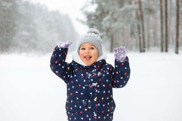 Nettes kleines mädchen, das spaß hat, draußen mit schnee zu spielen. schneebedecktes winterwetter.