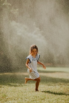 Nettes kleines mädchen, das spaß mit wasser unter bewässerungssprinkler hat