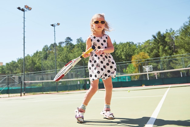 Nettes kleines mädchen, das tennis auf dem tennisplatz draußen spielt.