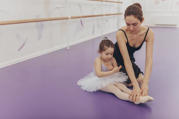 Nettes kleines mädchen, das tut und trikot trägt und mit ihrem lehrer an der ballettschule trainiert.