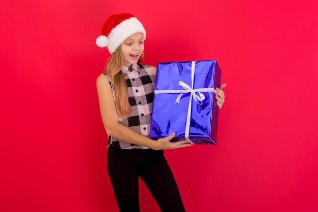 Nettes kleines mädchen, das weihnachtshut trägt, der lokal über rotem hintergrund steht und blaue geschenkbox hält