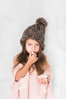 Nettes kleines mädchen, das winterhut isst und trägt