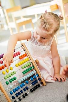 Nettes kleines mädchen, das zu hause mit hölzernem abakus spielt. intelligentes kind, das lernt zu zählen. vorschüler, der spaß mit pädagogischem spielzeug zu hause oder kindergarten hat.