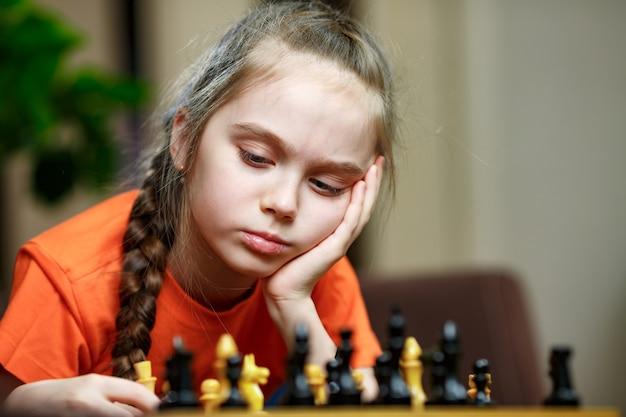 Nettes kleines mädchen, das zu hause schach spielt.