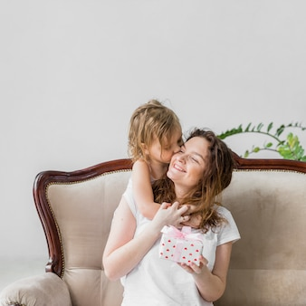 Nettes kleines mädchen, das zu ihrer mutter hält die geschenkbox sitzt auf sofa küsst