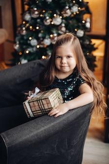 Nettes kleines mädchen des kindes mit langen haaren, die im sessel sitzen, der festliches weihnachtsgeschenk auf weihnachtsbaum hält.