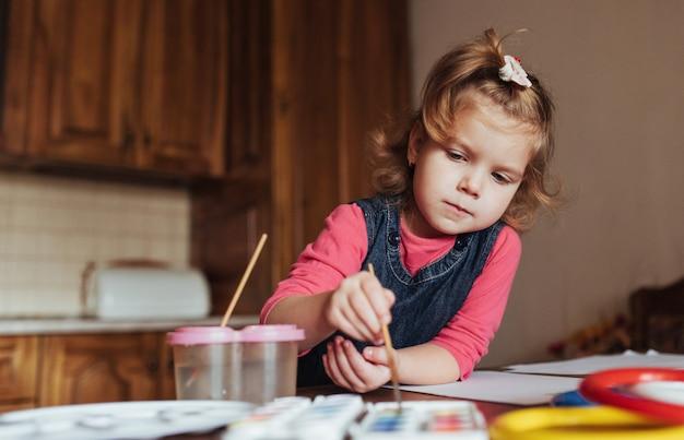 Nettes kleines mädchen, entzückendes vorschulkind, das mit aquarellen malt