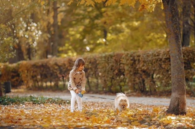 Nettes kleines mädchen geht in einem herbstpark mit einem hund
