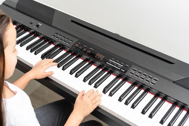 Nettes kleines mädchen hat kurs mit klavier