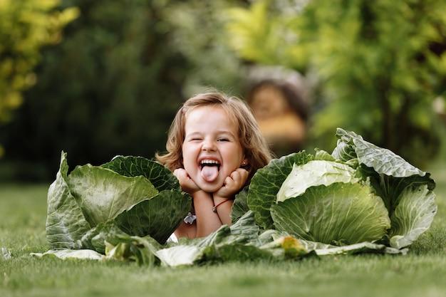 Nettes kleines mädchen hat spaß und liegt auf grünem gras in der nähe von kohl
