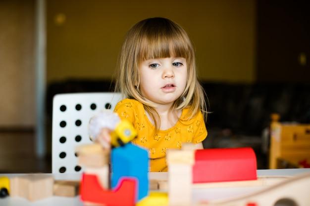 Nettes kleines mädchen im gelben kleid, das mit bunten ziegelsteinen spielt