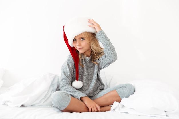 Nettes kleines mädchen im grauen pyjama, das die hut ihres flauschigen weihnachtsmanns berührt