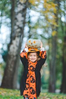 Nettes kleines mädchen im hexenkostüm für den feiertag von halloween. sie hält einen kürbis in ihren händen und steht im park.