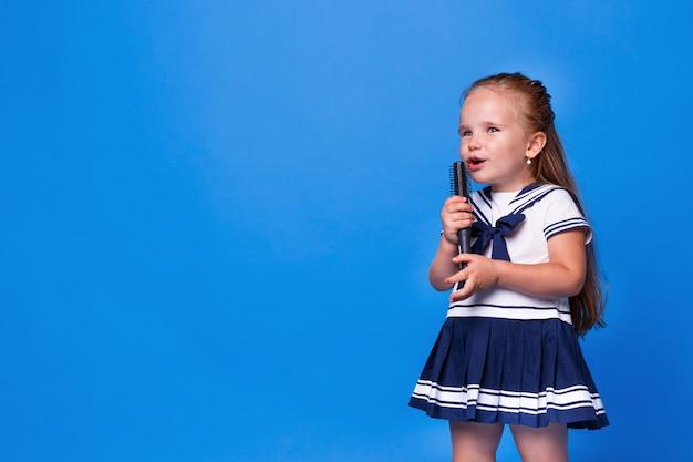 Nettes kleines mädchen im kleid, das einen kamm anstelle eines mikrofons auf blauem raum hält. platz für text. horizontale ansicht.