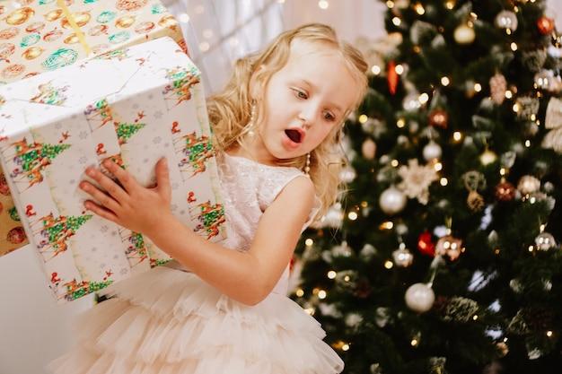Nettes kleines mädchen im rosa kleid mit geschenk auf hintergrund weihnachtsbaum. frohe weihnachten und ein gutes neues jahr und feiertage