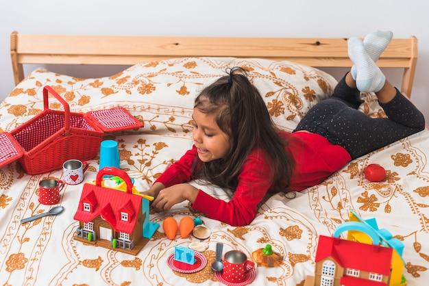 Nettes kleines mädchen im roten t-shirt-pullover mit langem hals, der mit ihren spielzeugen im schlafzimmer spielt.