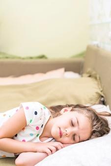 Nettes kleines mädchen im tupfen-trägershirt, der auf bett schläft