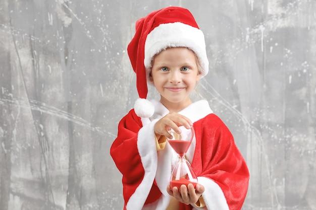 Nettes kleines mädchen im weihnachtsmann-anzug mit sanduhr auf schmutzhintergrund. weihnachts-countdown-konzept