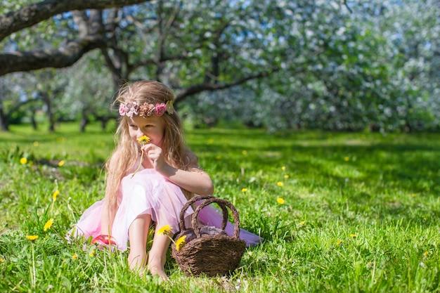 Nettes kleines mädchen in blühendem apfelgarten am sonnigen frühlingstag