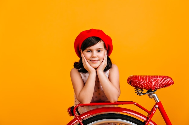 Nettes kleines mädchen in der französischen baskenmütze, die mit fahrrad aufwirft. lächelndes kind isoliert auf gelb.