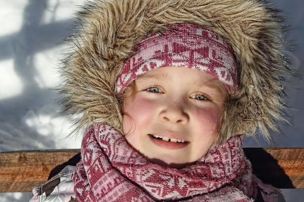 Nettes kleines mädchen in der rosa wintermütze und im schal