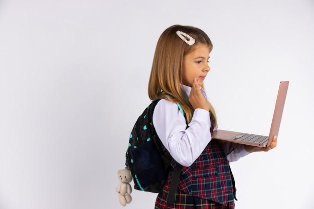 Nettes kleines mädchen in der schuluniform, die einen laptop hält, der hallo lokalisiert auf grauer wand zeigt. online-lernkonzept.