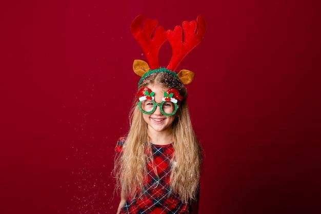 Nettes kleines mädchen in der weihnachtsbrille bläst schnee von palmen im studio auf einem roten hintergrund. weihnachtskonzept, textraum