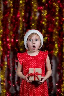 Nettes kleines mädchen in der weihnachtsmütze hält neujahrsgeschenk mit geschütteltem gesicht, das schaut.