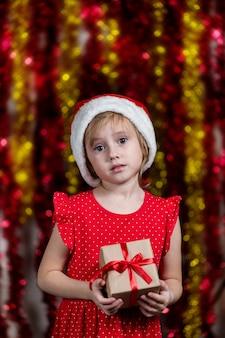 Nettes kleines mädchen in der weihnachtsmütze hält weihnachtsgeschenk und lächelt.