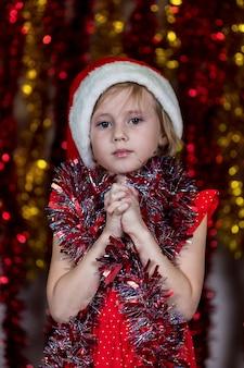 Nettes kleines mädchen in der weihnachtsmütze und mit lametta um den hals wunsch nach weihnachtsgeschenken.