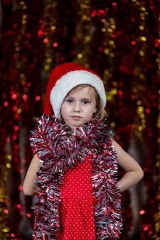 Nettes kleines mädchen in der weihnachtsmütze und mit lametta um ihren hals, das ernst schaut.