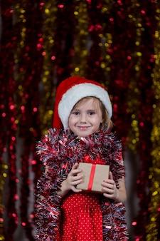 Nettes kleines mädchen in der weihnachtsmütze und mit lametta um ihren hals, der neujahrsgeschenk hält.