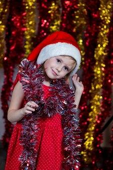 Nettes kleines mädchen in der weihnachtsmütze und mit lametta um ihren hals lächelnd.