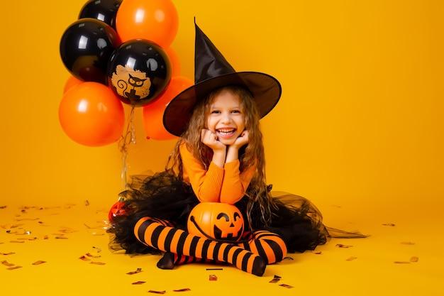 Nettes kleines mädchen in einem hexenkostüm für halloween