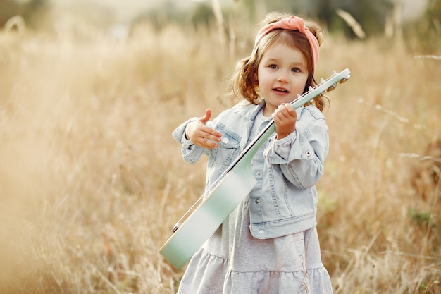 Nettes kleines mädchen in einem park, der auf einer gitarre spielt