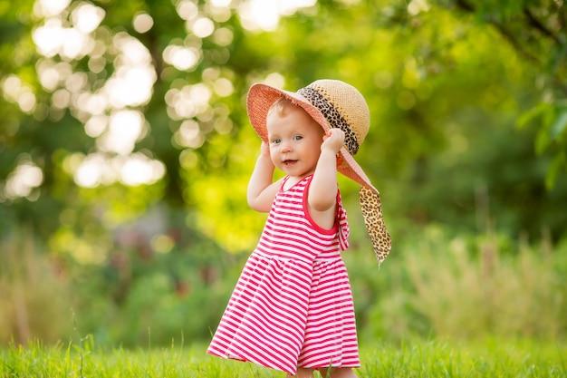 Nettes kleines mädchen in einem roten kleid und hut geht im sommer barfuß auf dem grünen gras