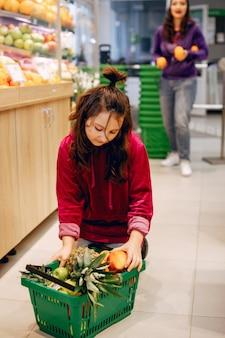 Nettes kleines mädchen in einem supermarkt