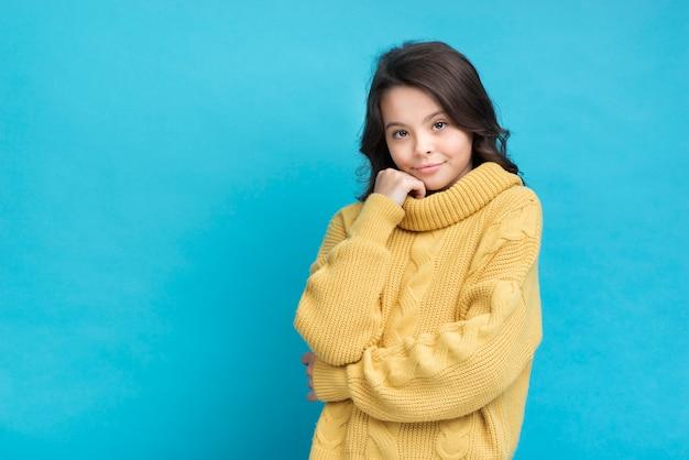 Nettes kleines mädchen in einer gelben strickjacke auf blauem hintergrund