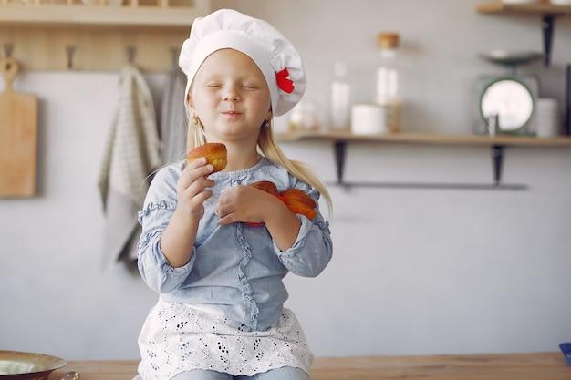 Nettes kleines mädchen in einer küche mit kleinem kuchen