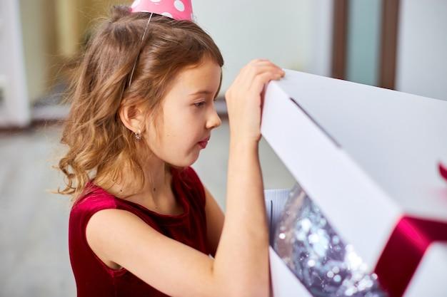 Nettes kleines mädchen in rosa kleid und hut öffnen große geschenkbox mit luftballons zu hause geburtstagsparty-streamer, alles gute zum geburtstag. feiern