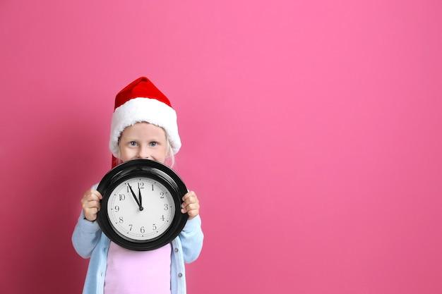 Nettes kleines mädchen in weihnachtsmütze mit uhr auf farbhintergrund. weihnachts-countdown-konzept