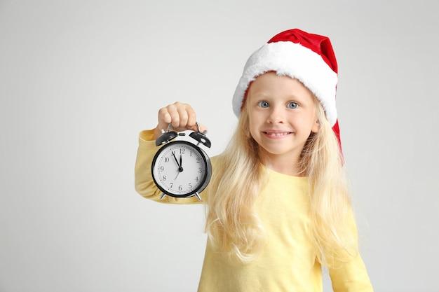 Nettes kleines mädchen in weihnachtsmütze mit uhr auf heller oberfläche. weihnachts-countdown-konzept